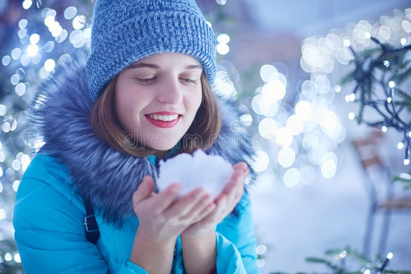 Outdoor shot of glad smiling beautiful woman has red lips and attractive appearance, holds white snow in hands, admires winter won. Derful magic night city and royalty free stock images