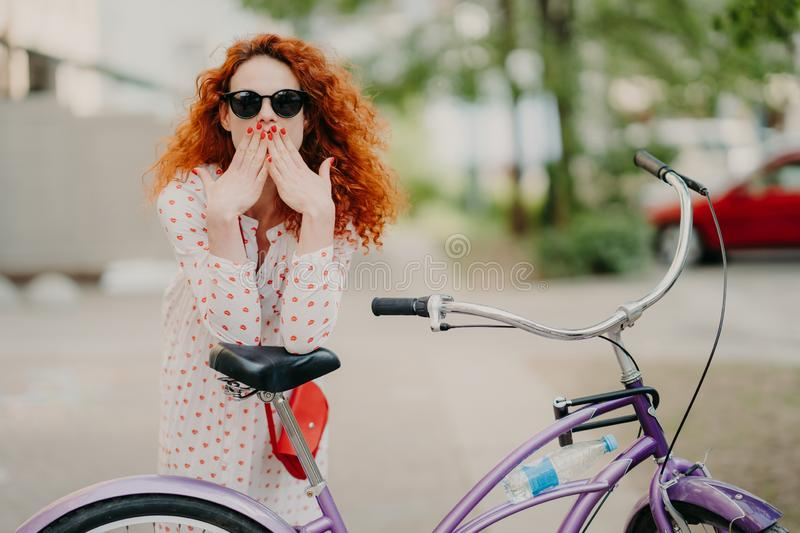Outdoor shot of gorgeous red haired female covers mouth with both palms, has red manicure, dressed in fashionable dress and trendy royalty free stock photo