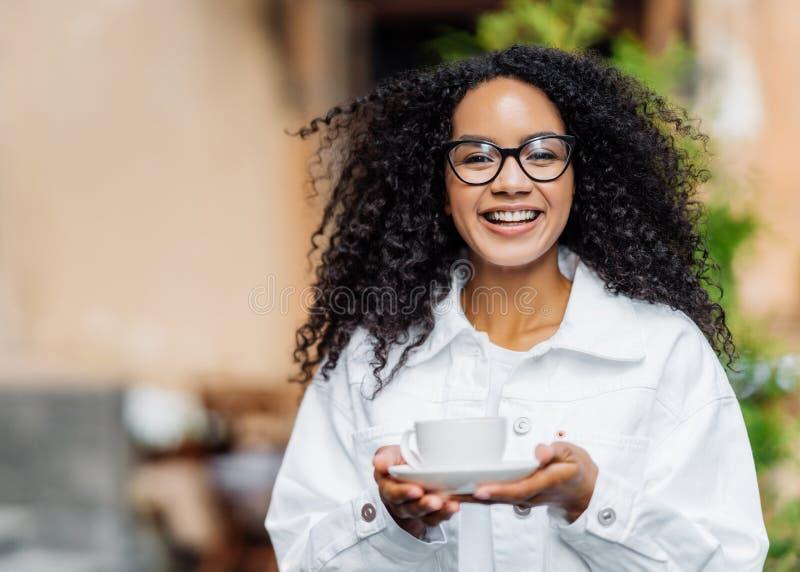 Outdoor shot of happy dark skinned lady with crisp hair, wears white jacket, drinks hot tea, has stroll across street, happy royalty free stock photos