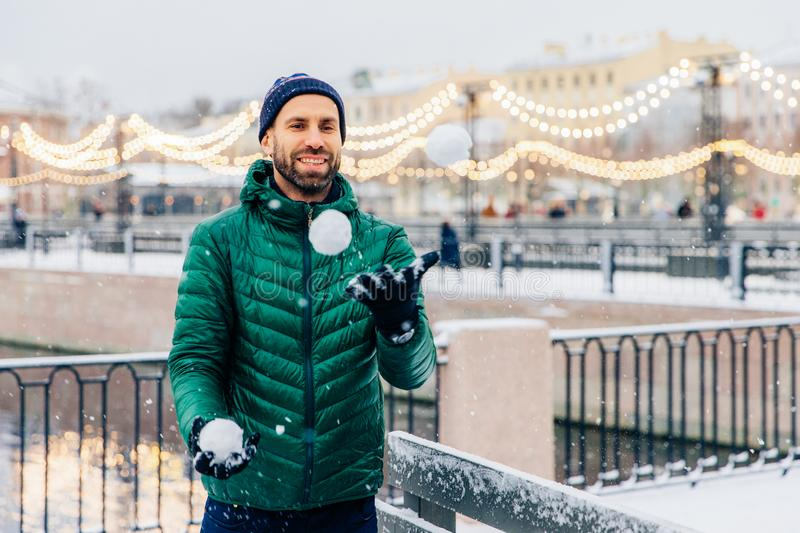 Outdoor shot of happy smiling bearded male in warm jacket and ha stock images