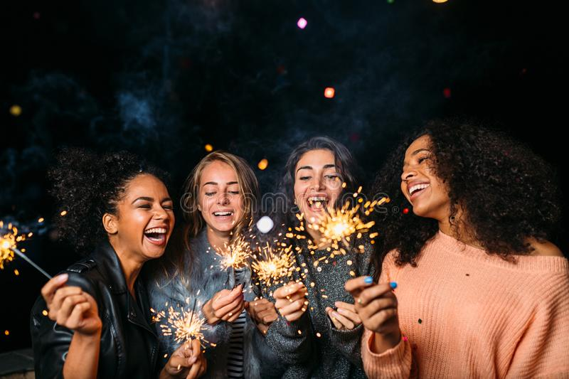 Outdoor shot of laughing friends with sparklers. Standing together at night stock images