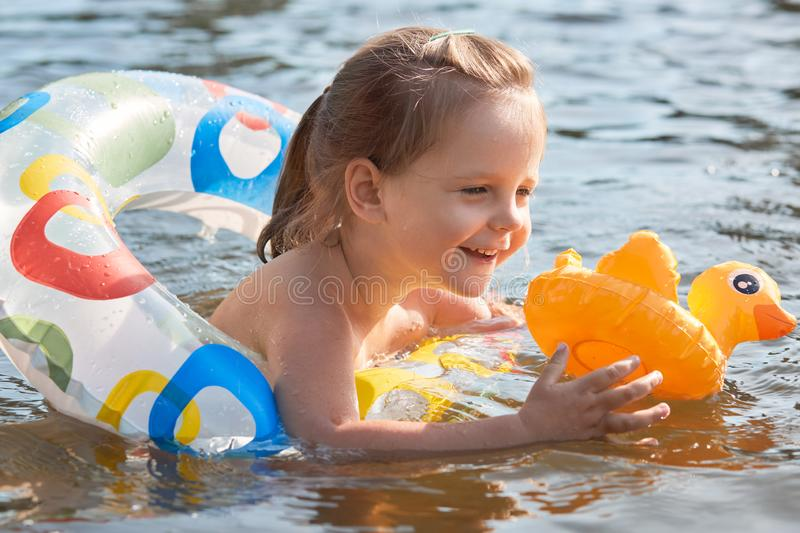 Outdoor shot of liitl girl in lifebuoy, happy child swims in pond, todler in rubber ring having fun in river, holds yellow duck, stock images