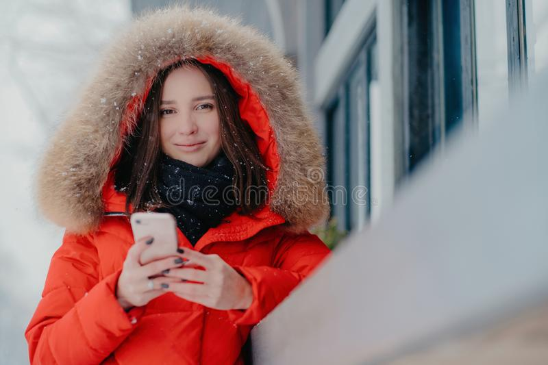 Outdoor shot of lovely dark haired Caucasian woman in winter street clothes, holds modern cell phone, reads received message, royalty free stock photography