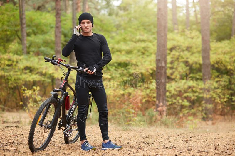 Outdoor shot of man wearing black track suit and sneakers, standing near his mountain bike and speaks phone with beautiful forest royalty free stock image