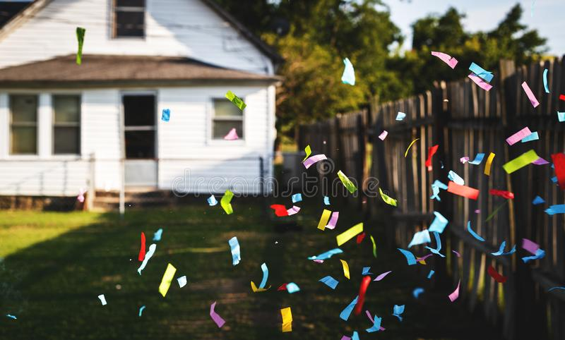 Celebrate Being Outdoors. Outdoor shot of multi-colored paper confetti in front of the camera just after being expelled from a cannon type launcher with a house royalty free stock photo
