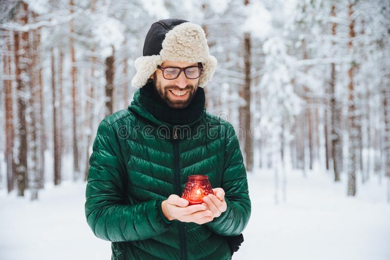 Outdoor shot of pleasant looking male holds candle in hands, warms hands, looks happily on it as stands in winter forest covered w. Ith snow. Positive young stock images