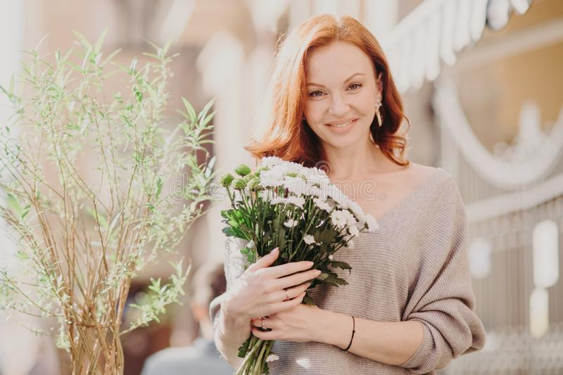 Outdoor shot of pleasant looking young ginger female with satisfied expression, wears brown jumper, holds bouquet of white flowers stock photos