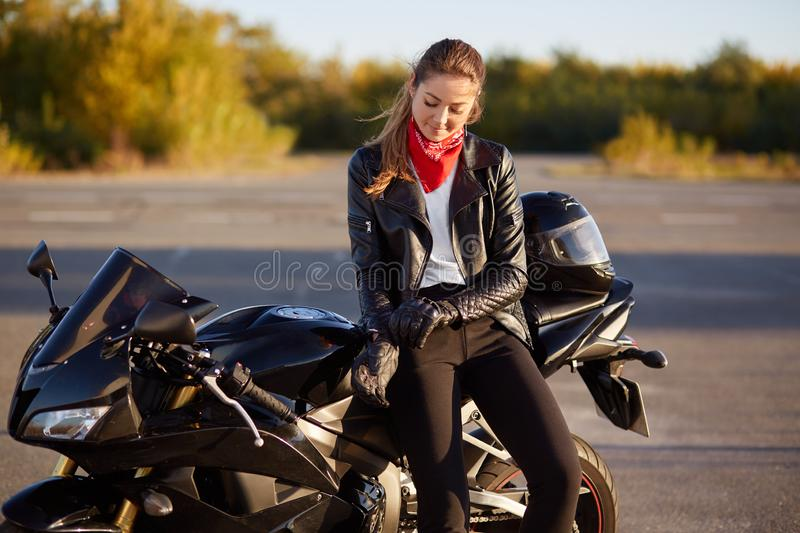 Outdoor shot of pleased female bikes puts on leather gloves, dressed in black clothes, poses on motorbike, prepares for racing or royalty free stock image