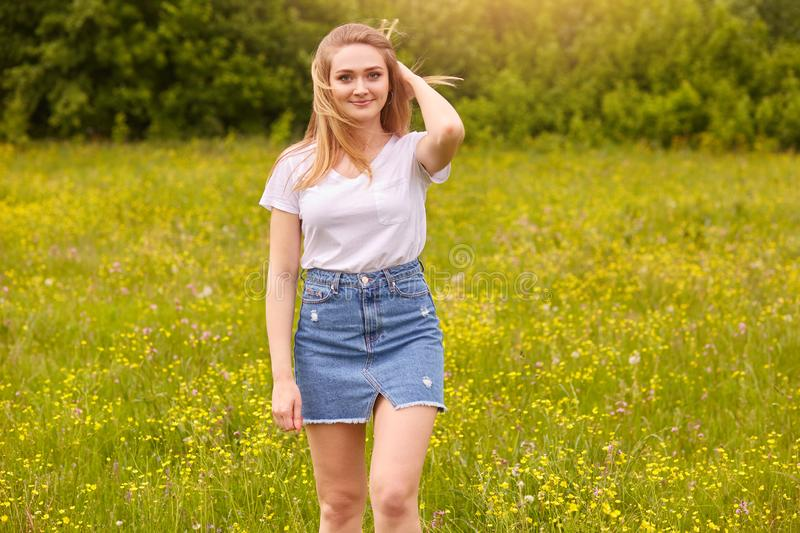 Outdoor shot of pretty blond woman wearing white casual t shirt and denim skirt, posing in meadow, touching her fair hair, looking stock images