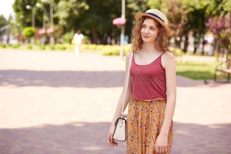 Outdoor shot of romantic adorable model with fair curly hair standing in local park, spending time around nature with pleasure, stock image