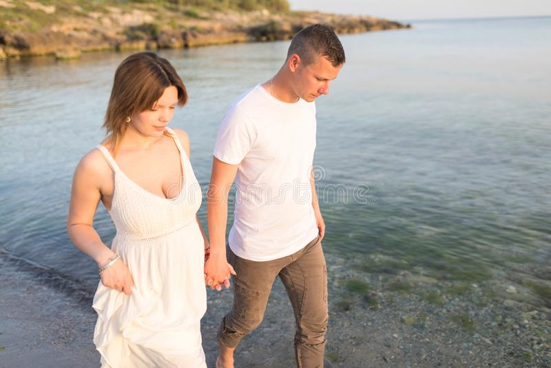 Outdoor shot of romantic young couple walking along the sea shore holding hands. Young men and women walking on the beach together at sunset, body closeup stock images