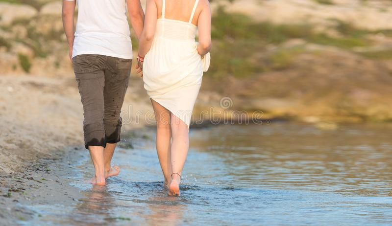 Outdoor shot of romantic young couple walking along the sea shore holding hands. Young men and women walking on the beach together at sunset, body closeup stock photography