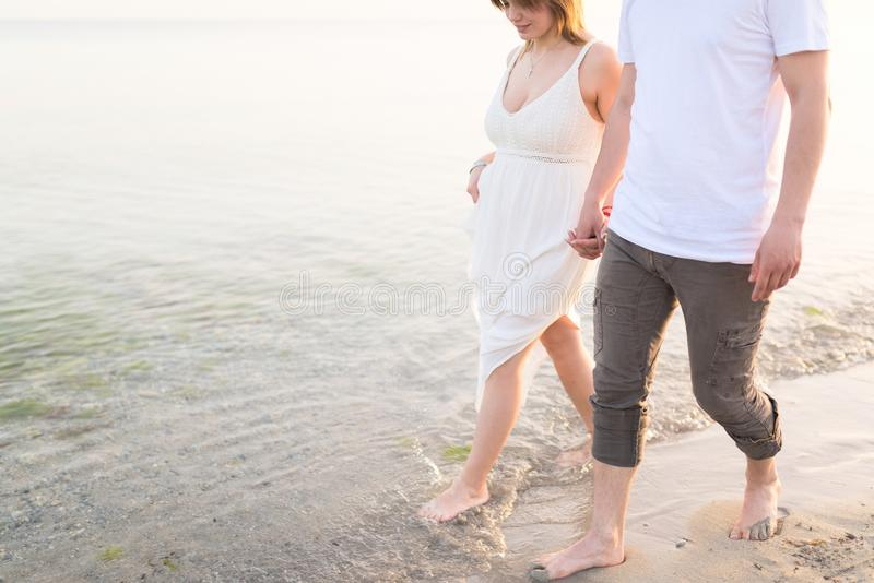 Outdoor shot of romantic young couple walking along the sea shore holding hands royalty free stock photos