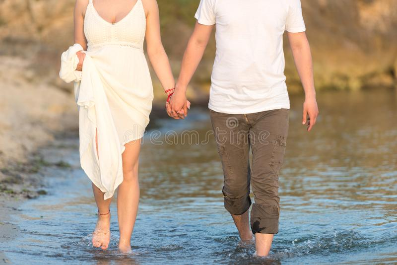 Outdoor shot of romantic young couple walking along the sea shore holding hands. Young men and women walking on the beach together at sunset, body closeup royalty free stock images