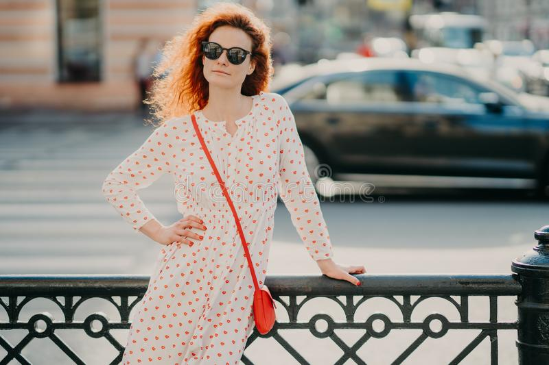 Outdoor shot of satisfied redhead woman keeps one hand on waist, other on street hence, poses over blurred urban setting, wears royalty free stock images