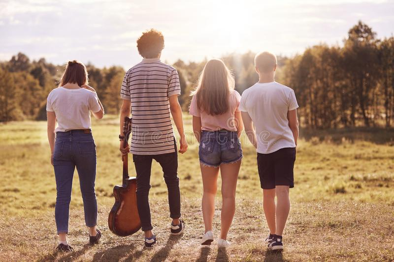 Outdoor shot of teenagers stand backs to camera, have walk on field, recreat during summer holidays, use guitar for singing songs,. Being photographed in motion royalty free stock photography