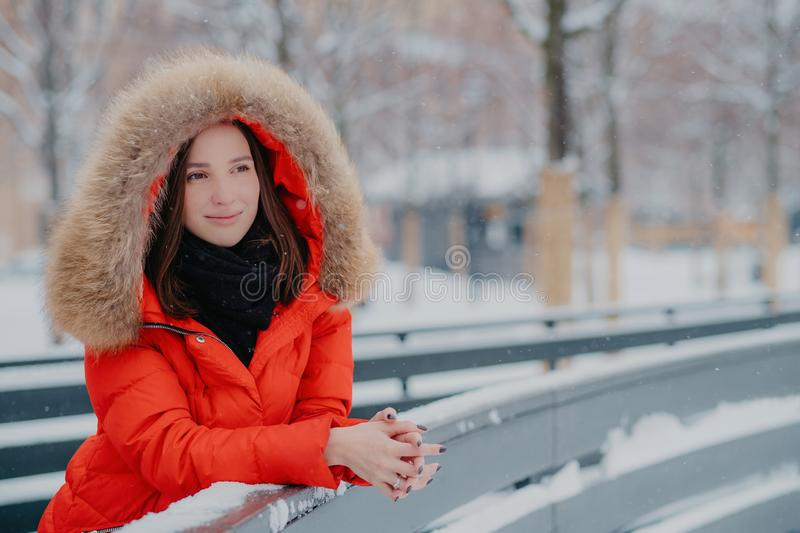Outdoor shot of thoughtful European woman wears red winter jacket with hoody on head, leans on hence, looks pensively into stock images