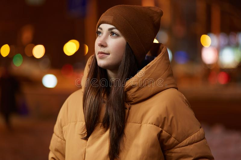 Outdoor shot of thoughtful young woman wears stylish hat and brown jacket, has pensive facial expression, enjoys calm atmosphere stock photos