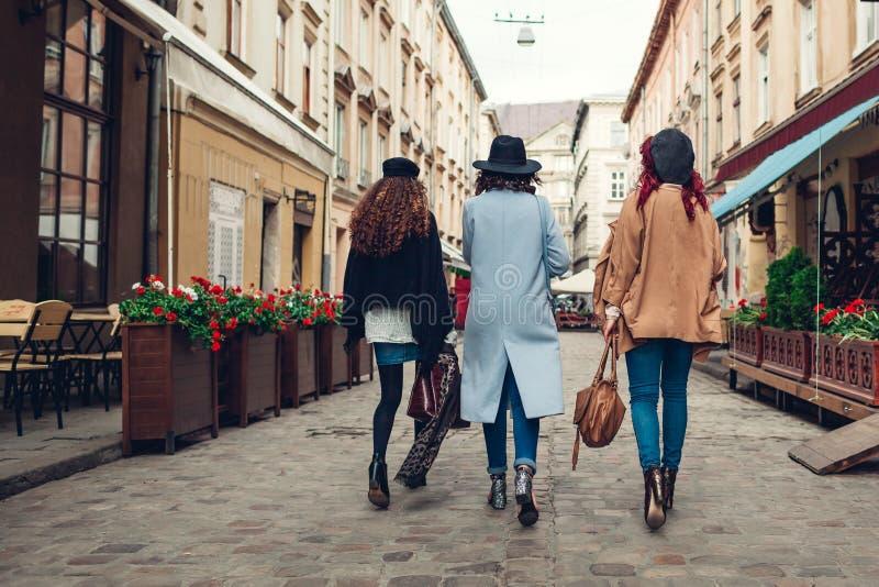 Outdoor shot of three young women walking on city street. Girls having fun. Back view stock photography