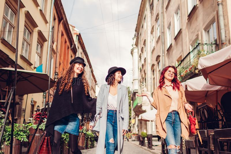 Outdoor shot of three young women walking on city street. Girls talking and having fun stock images