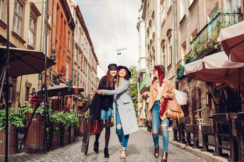 Outdoor shot of three young women walking on city street. Girls talking and hugging royalty free stock photography
