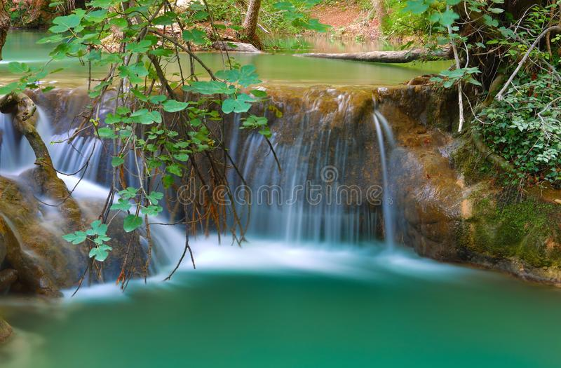 Waterfall with long exposure for an effect spun in the middle of the green nature. Outdoor shot in a wet undergrowth with waterfalls and use of a big stopper for stock photography