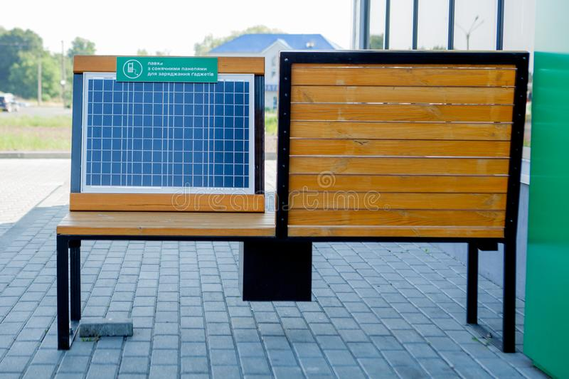 Outdoor shot of wooden bench in park having solar power panel installed, USB cabel connected to smartphone.  stock photos