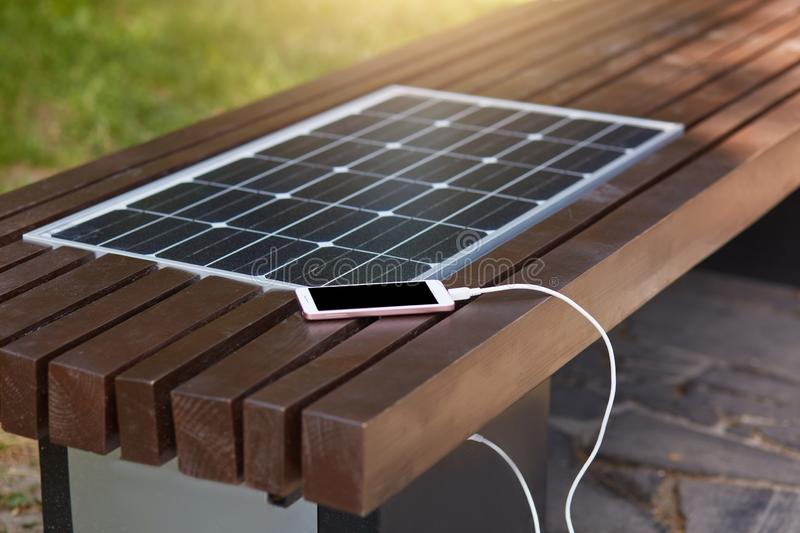 Outdoor shot of wooden bench in park having solar power panel installed, USB cabel connected to smartphone, modern device lying. Near solar panel charging stock image