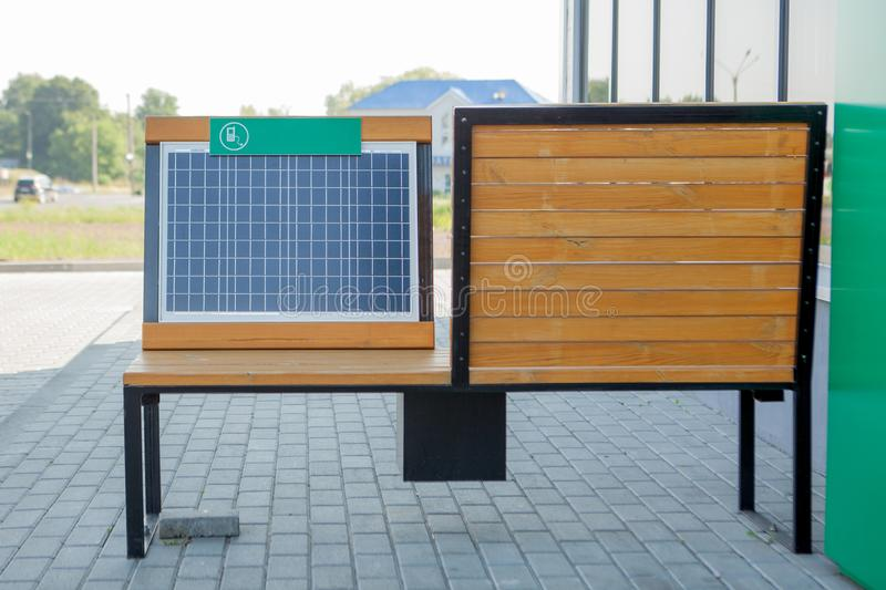 Outdoor shot of wooden bench in park having solar power panel installed, USB cabel connected to smartphone.  stock image