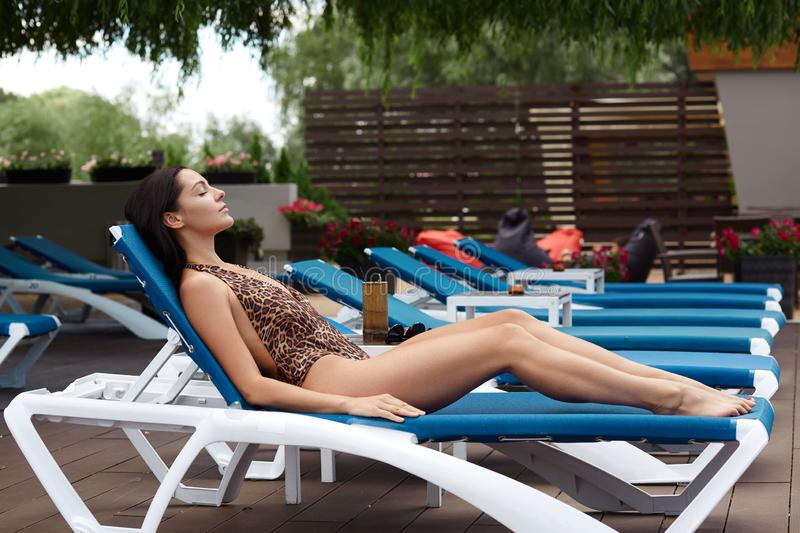 Outdoor shot of young slim woman laying on lounge, lady spending sunny day, attractive female with tanned skin and beautiful body stock photos