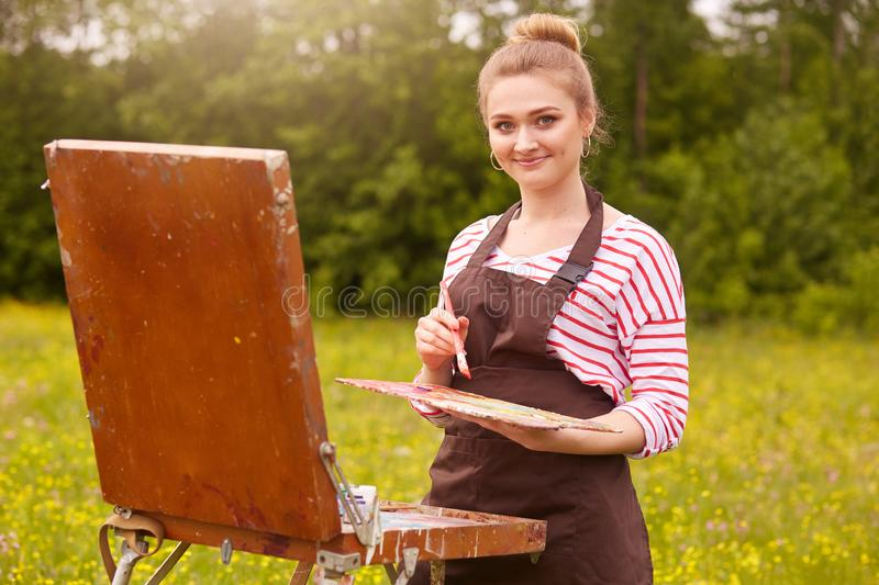 Outdoor shot of young woman artist standing with sketchbook against meadow background, holding brush and palette of colours, stock photography