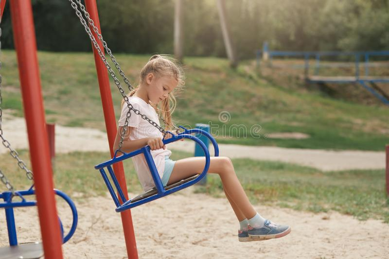 Outdoor shotof charming little girl on playground having fun at summer time,waiting for friend for playing, posing alone, cute royalty free stock photos