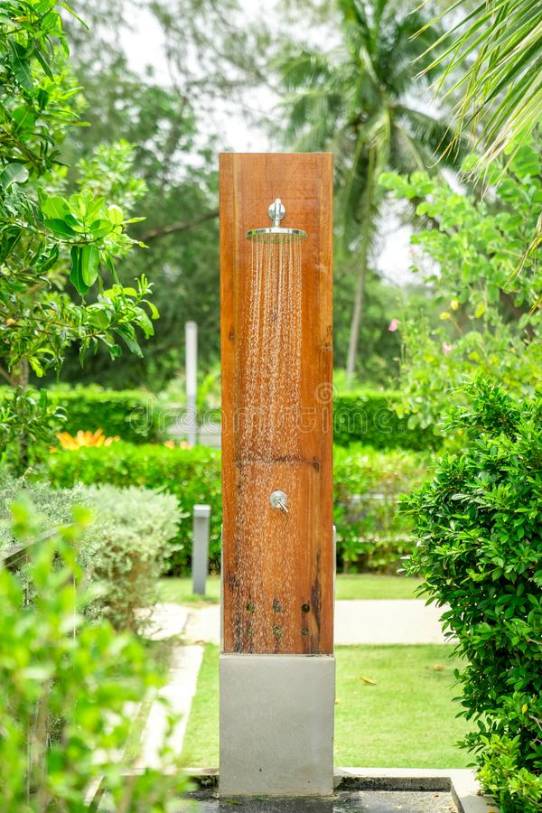 Outdoor shower head stick on the wooden plate pole design for showering body before jumping in the resort pool. Outdoor shower head  stick on the wooden plate royalty free stock photography