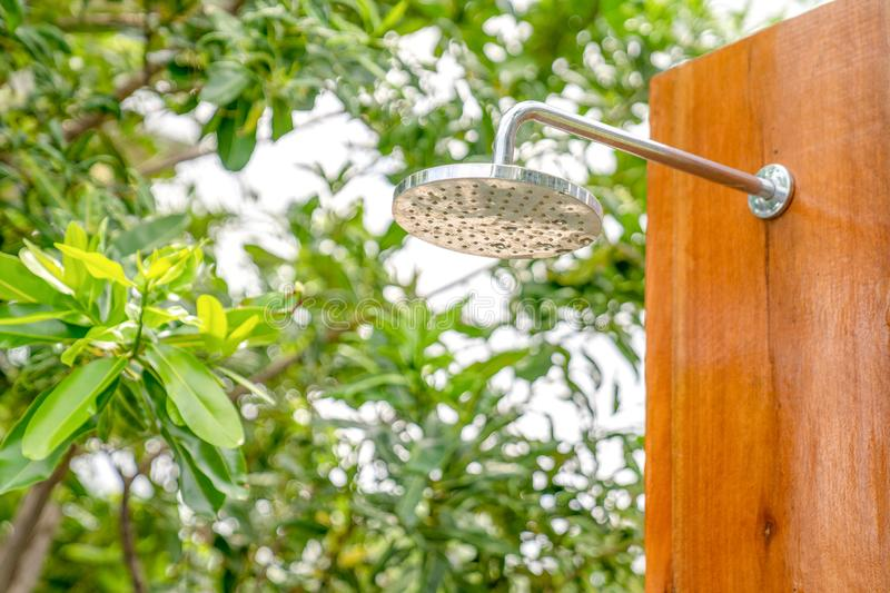 Outdoor shower head stick on the wooden plate pole design for showering body before jumping in the resort pool. Outdoor shower head  stick on the wooden plate royalty free stock image