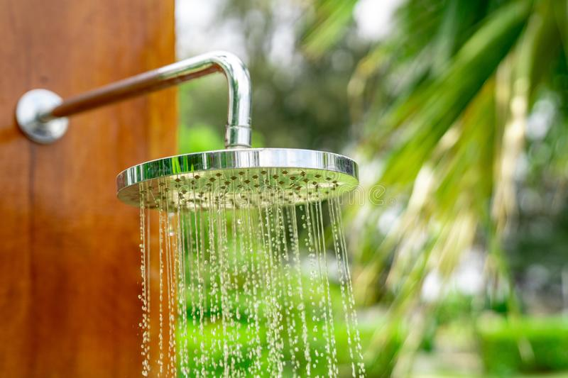 Outdoor shower head stick on the wooden plate pole design for showering body before jumping in the resort pool. Outdoor shower head  stick on the wooden plate royalty free stock photos