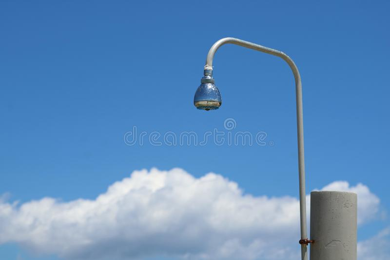 Outdoor showering shower head against blue sky with clouds at beach stock photos