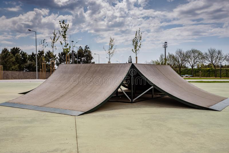 Outdoor skatepark with various ramps  with a cloudy sky.  stock images