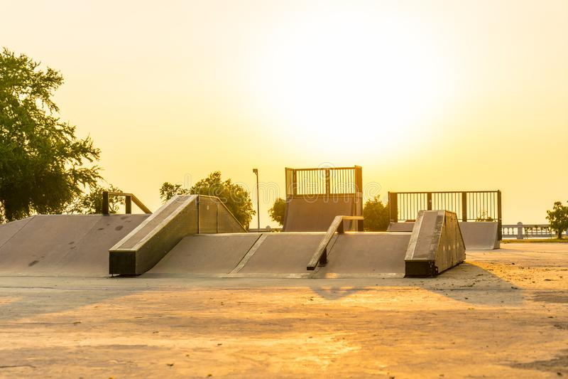 Outdoor skatepark with various ramps on sunset time.  stock image