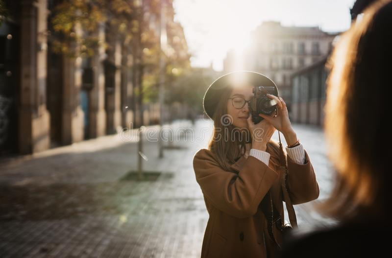 Outdoor smiling lifestyle portrait of pretty young woman having fun in sun city Europe autumn with camera travel photo royalty free stock photo