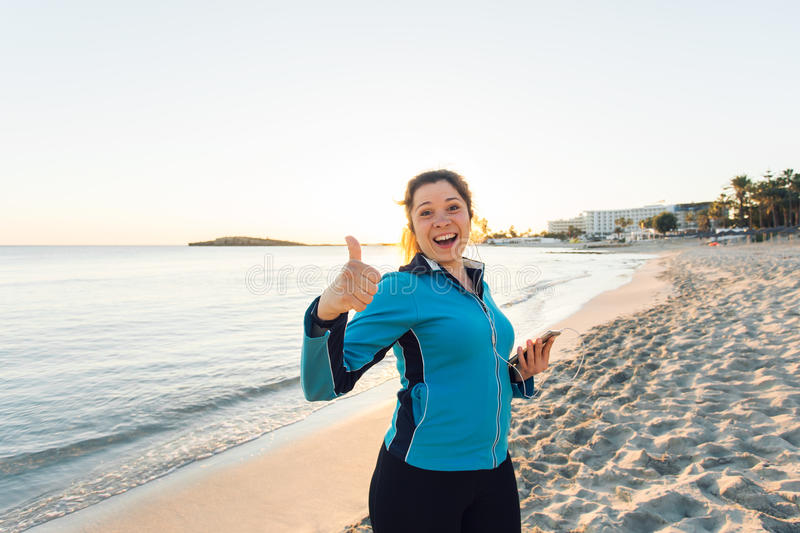 Outdoor sport, fitness gadget and people concept - Smiling female fitness show thumbs up and holding smartphone with stock photography