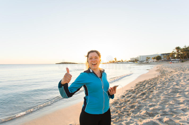 Outdoor sport, fitness gadget and people concept - Smiling female fitness show thumbs up and holding smartphone with stock photo