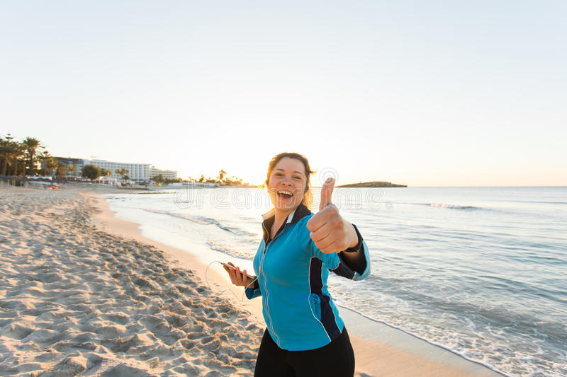 Outdoor sport, fitness gadget and people concept - Smiling female fitness show thumbs up and holding smartphone with royalty free stock photography
