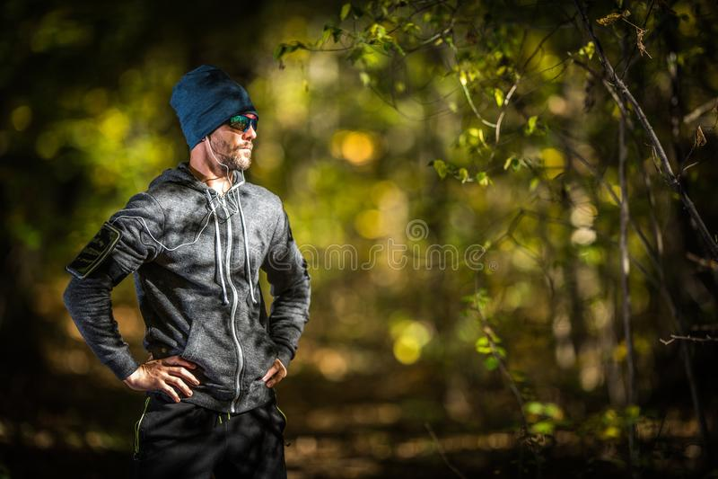 Outdoor Sportsman Runner. Caucasian Men in His 30s with Headphones on the Late Afternoon Jogging in the Forest. Outdoor Sportsman Runner royalty free stock photography
