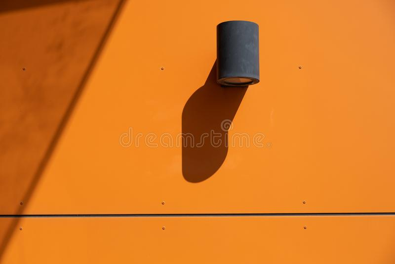 Outdoor spotlight lamp mounted on orange wall. stock photography
