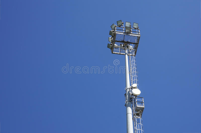 Outdoor stadium lights and telecommunication tower against daytime blue sky. stock image