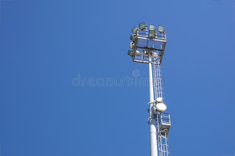 Outdoor stadium lights and telecommunication tower against daytime blue sky. royalty free stock photos