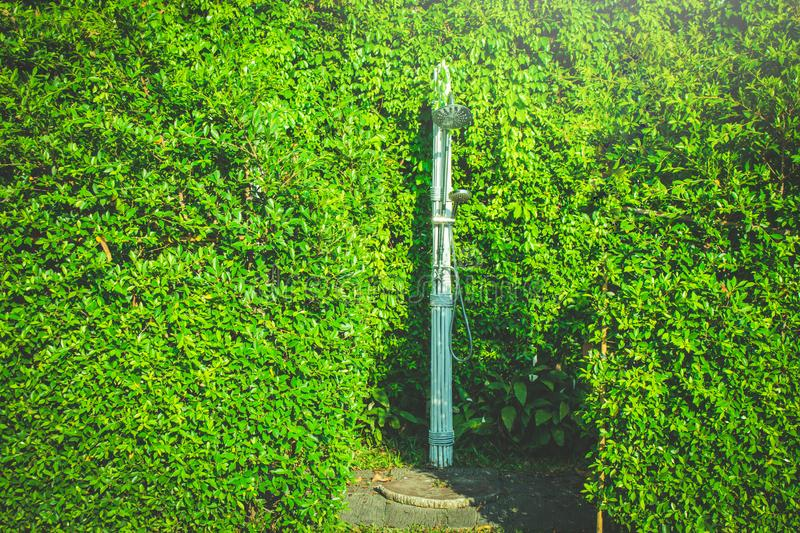 Outdoor stainless shower surrounded with green trees for take a bath before play and swim in swimming pool. Selective focus royalty free stock images