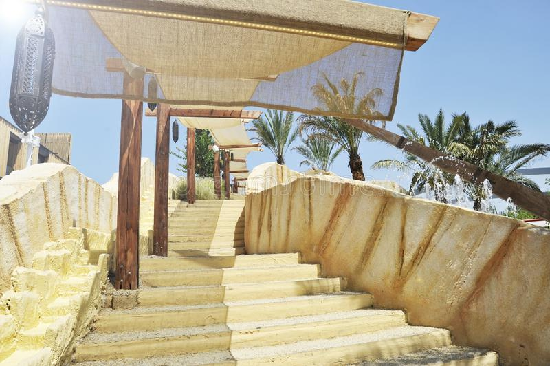 Outdoor stairway with a sun tent. In the background there are palm trees and fountain jets of water. A typical Arab lamp is. Hanging royalty free stock images