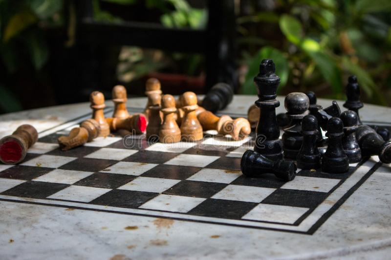 Outdoor stone chessboard with black and yellow figures. Competition and strategy concept. Chess wooden pieces on board in sunlight. Outdoor stone chessboard with royalty free stock photos