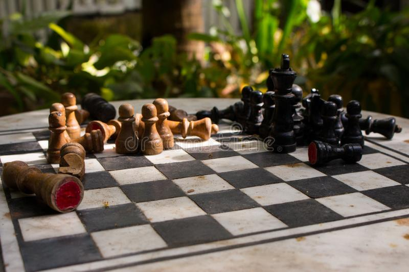 Outdoor stone chessboard with black and yellow figures. Competition and strategy concept. Chess wooden pieces on board in sunlight. Outdoor stone chessboard with stock photography